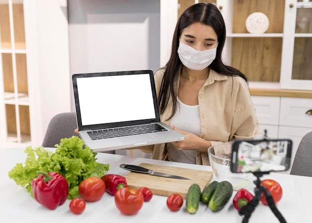 Vlogging feminino em casa com vegetais e laptop