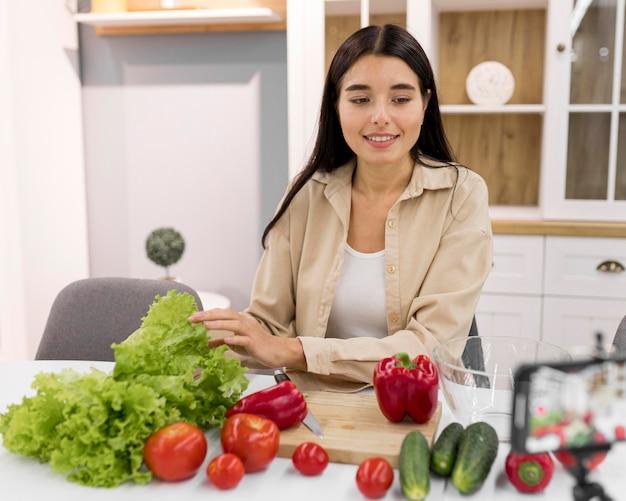 Vlogging feminino em casa com vegetais e smartphone