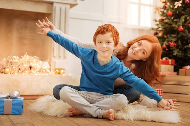 Voando alto. foco seletivo em um menino ruivo sorrindo alegremente enquanto está sentado no chão com sua mãe e fingindo voar como um avião.