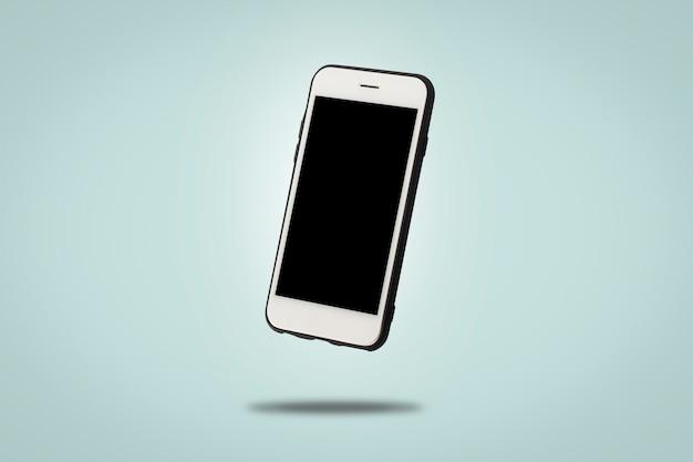 Voando celular branco sobre uma superfície azul. levitação. aplicações de conceito para telefone, dispositivo móvel, apresentação.