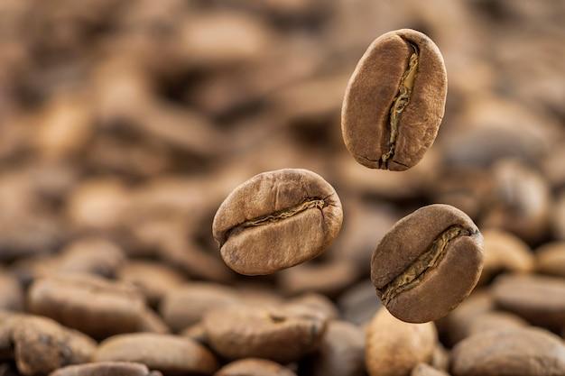 Voando grãos de café frescos como pano de fundo com espaço de cópia. grãos de café caindo com vapor de vapor branco.