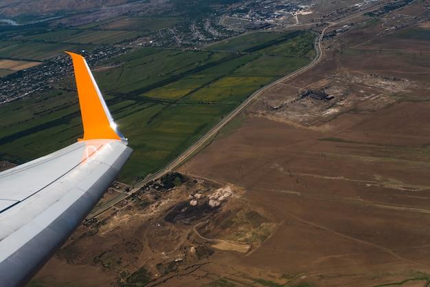 Voar e viajar asa de um avião voando acima do solo bela vista da janela do avião ... Foto Premium