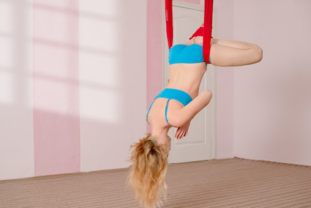Voar yoga. a menina realiza exercícios de ioga aérea