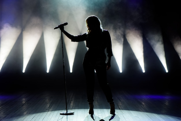Vocalista cantando ao microfone. cantor em silhueta