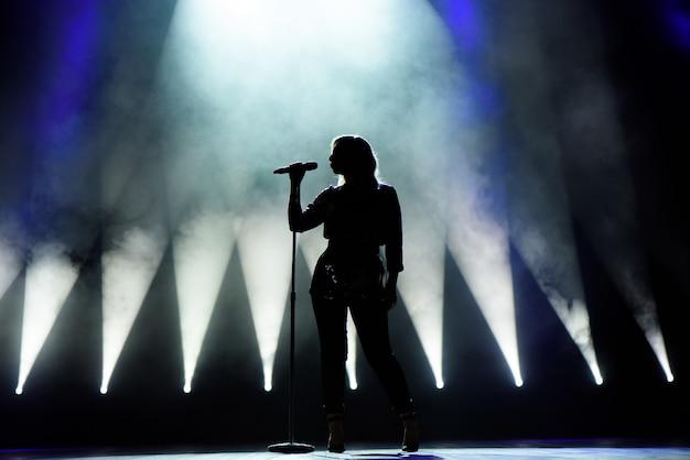 Vocalista cantando ao microfone. cantora em silhueta.