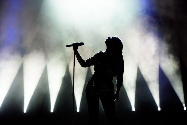 Vocalista cantando para microfone. cantor em silhueta