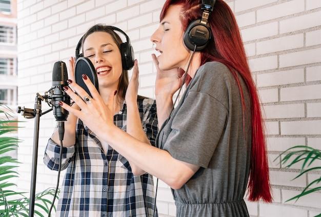 Vocalistas cantando em estúdio profissional