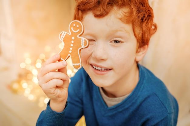 Você consegue me ver. vista superior de um adorável garoto ruivo se divertindo e fazendo caretas enquanto brincava com um boneco de gengibre caseiro.