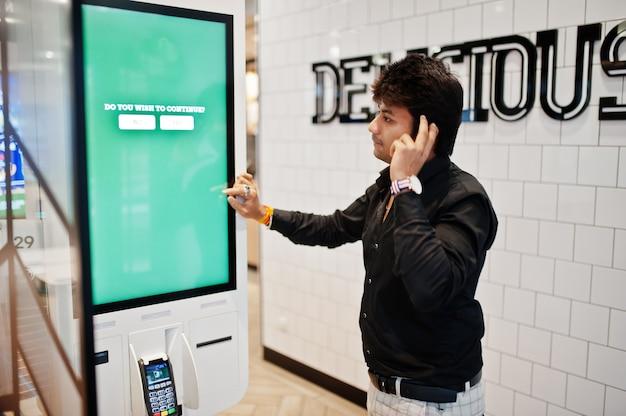 Você deseja continuar? o cliente indiano do homem na loja coloca ordens e paga através do quiosque do assoalho do auto-pagamento para o fast food, terminal de pagamento. seu pensamento de escolha.