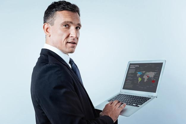 Você disse alguma coisa. foto de um empresário de sucesso virando a cabeça e olhando para a câmera com confiança, segurando um laptop e trabalhando duro em um projeto internacional da cintura para cima.