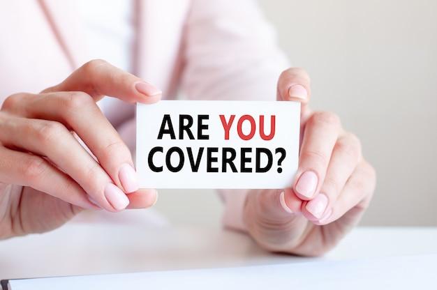 Você está coberto está escrito em um cartão de visita branco nas mãos de uma mulher.