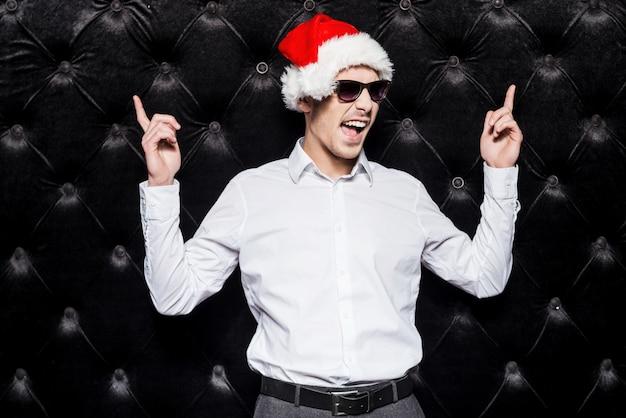 Você está pronto para a festa? jovem bonito com óculos escuros e chapéu de papai noel apontando para cima e expressando positividade em pé contra um fundo preto