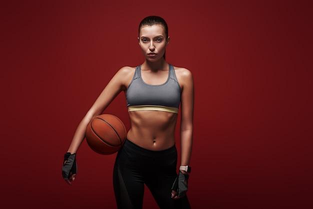 Você está pronto para jogar esportista? está treinando com a bola em pé sobre o fundo vermelho