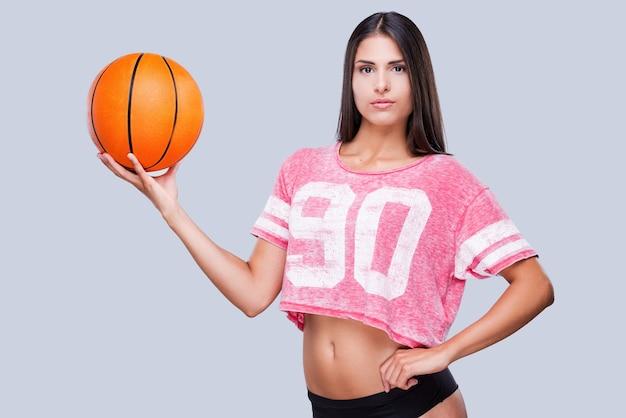 Você esta pronto para jogar? linda jovem líder de torcida segurando uma bola de basquete e olhando para a câmera em pé contra um fundo cinza