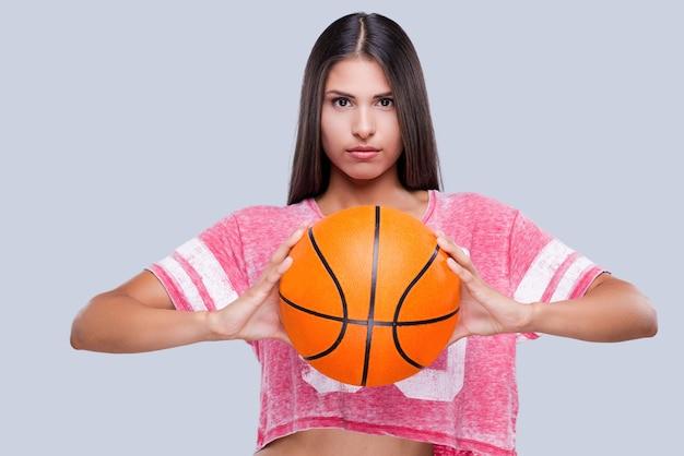 Você está pronto para o jogo? jovem líder de torcida confiante segurando uma bola de basquete e olhando para a câmera em pé contra um fundo cinza
