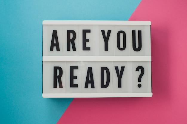 Você está pronto - texto em uma tela na superfície brilhante azul e rosa.