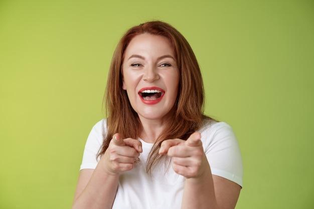 Você fez o melhor, amigável, alegre, entusiasmado, ruiva, gengibre, mulher, de meia idade, apontando, dedo indicador, câmera, dedo, pistola, gesto, sorrindo amplamente, parabenizar, torcedor, colega de trabalho, estande parede verde