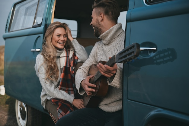 Você gosta dessa música? jovem bonito tocando violão para sua linda namorada enquanto está sentado em uma mini van azul estilo retro