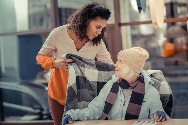 Você gostaria de alguma coisa. mulher simpática e gentil conversando com seu convidado enquanto cuida dela