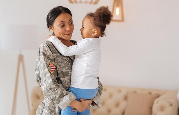 Você não vai acreditar. emocional mãe feliz e brilhante dizendo o quanto sente falta de sua princesinha e segurando-a com força em seus braços