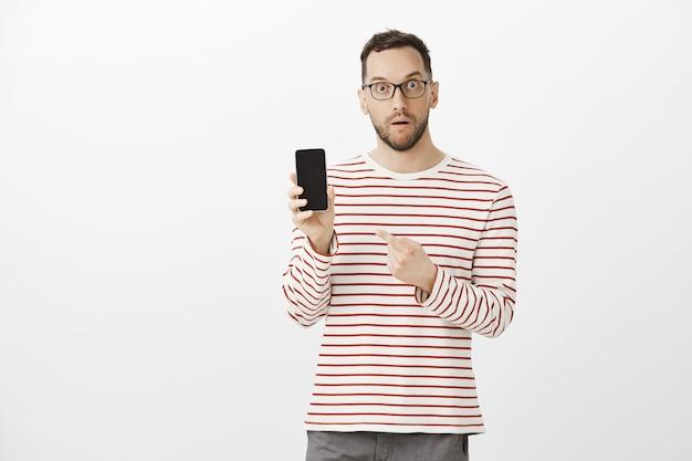 Você pode acreditar que tal perfeição existe. retrato de homem bonito surpreso e surpreso com óculos da moda
