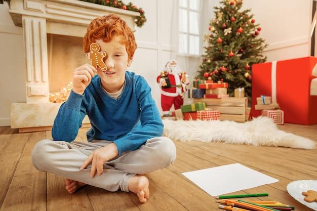 Você pode me ver agora. menino pré-adolescente alegre sentado no chão com as pernas cruzadas e brincando com um boneco de gengibre