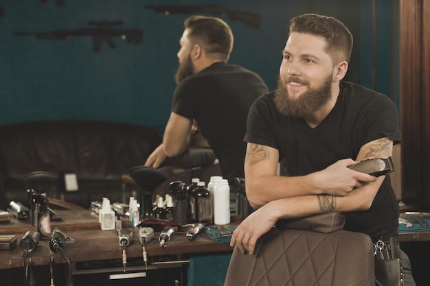 Você precisa de um corte de cabelo! barbeiro profissional, sorrindo, olhando para longe, posando em sua barbearia com um aparador na mão