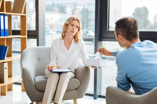 Você precisa de um. médica simpática e simpática olhando para o paciente e oferecendo lenços de papel enquanto tenta acalmá-lo