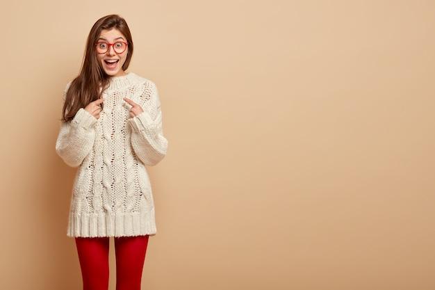 Você quer dizer eu, realmente? mulher européia positiva aponta para si mesma, surpresa por ser escolhida, olha com olhos cheios de alegria, usa óculos transparentes