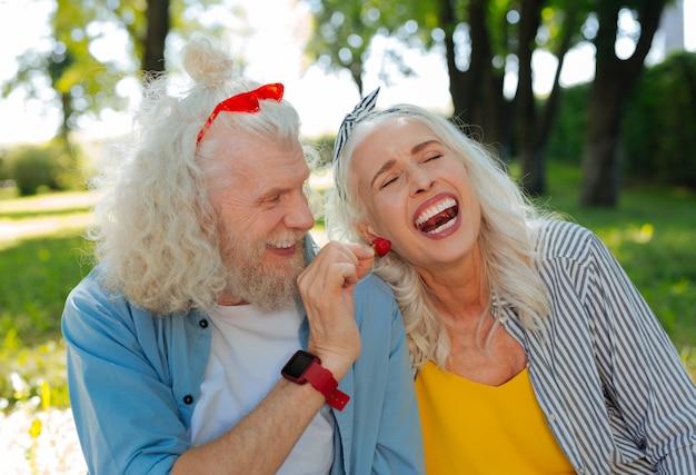 Você quer. homem alegre e feliz olhando para sua esposa enquanto lhe oferece um morango