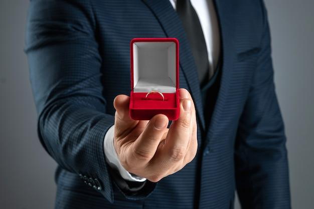 Você quer se casar comigo? um homem em um terno de negócio segura na mão uma caixa vermelha com uma aliança de casamento.