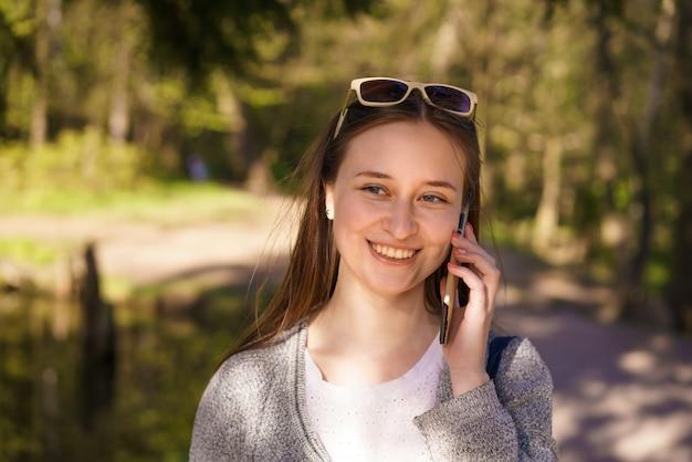 Você, uma linda jovem com óculos de sol anda e fala ao telefone em um dia ensolarado de primavera