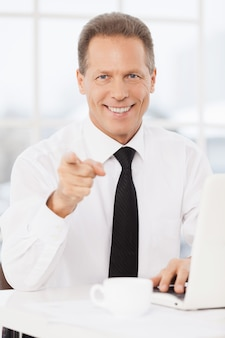 Você vai se juntar à minha equipe? homem maduro alegre de camisa e gravata apontando para a câmera e sorrindo