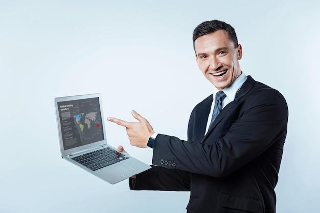 Você viu. cintura para cima foto de um homem de mente positiva, mostrando uma apresentação de transferências comerciais globais enquanto posava com um laptop e olhando para a câmera com um sorriso brilhante no rosto.