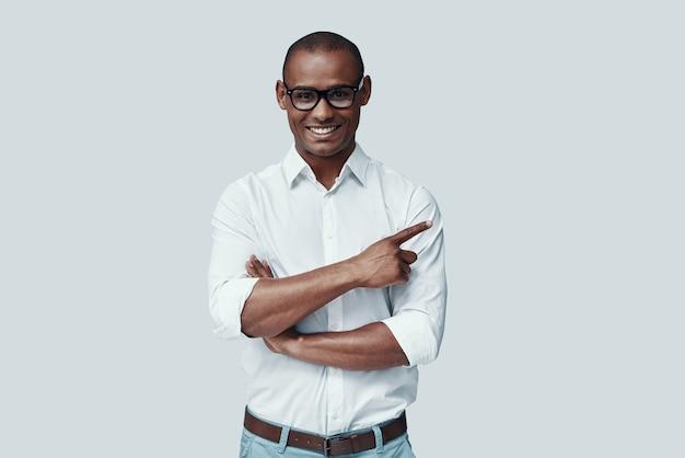 Você viu isso? africano jovem e bonito apontando para o espaço da cópia e sorrindo em pé contra um fundo cinza