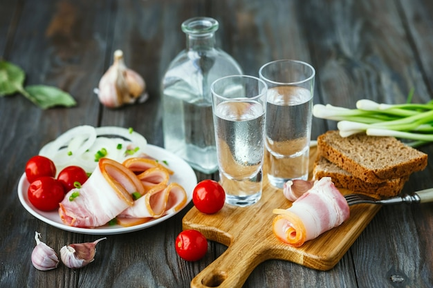 Vodka com banha e cebola verde na mesa de madeira
