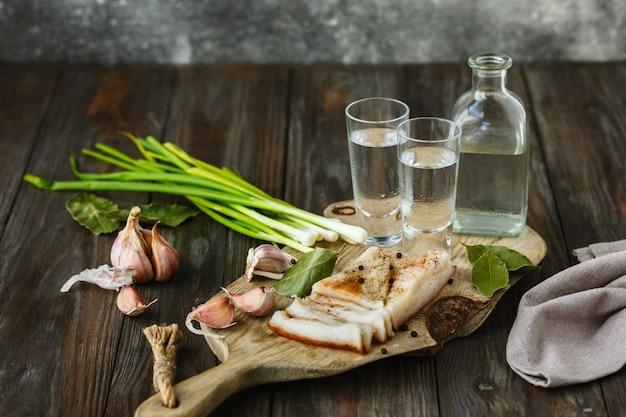 Vodka com banha e cebola verde na mesa de madeira.