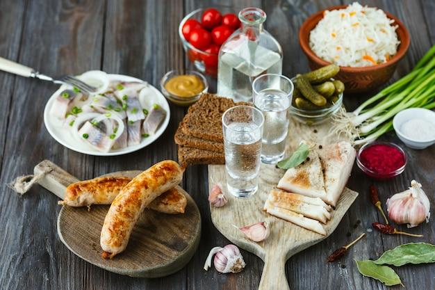 Vodka com banha, peixe salgado e legumes, salsichas na superfície de madeira. álcool bebida artesanal pura e lanche tradicional, tomate, repolho, pepino. espaço negativo. comemorando comida e deliciosa.