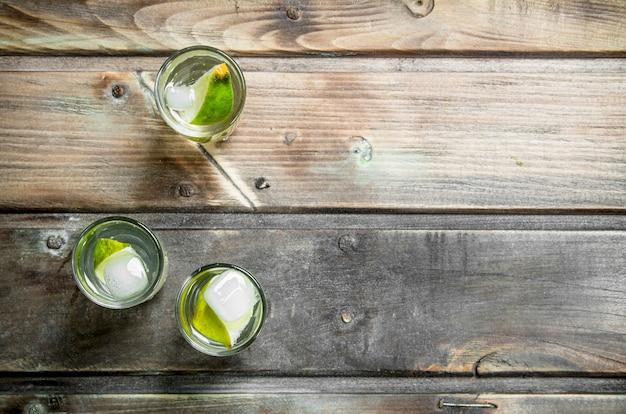 Vodka com fatias de limão e gelo.