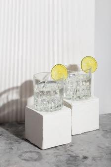 Vodka com gelo e limão em dois copos no suporte branco. sombras e luz do sol na moda