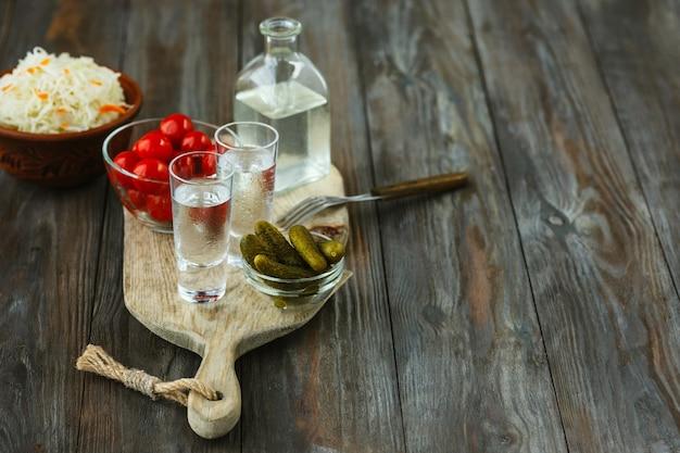 Vodka com legumes salgados na superfície de madeira. álcool bebida artesanal pura e lanche tradicional, tomate, repolho, pepino. espaço negativo. comemorando comida e deliciosa.