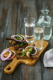 Vodka com torrada de peixe e pão na mesa de madeira