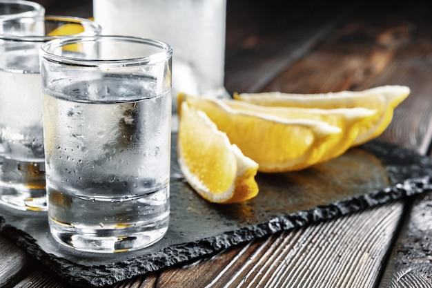 Vodka em copos de shot em fundo de madeira rústico