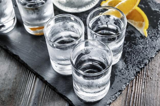 Vodka em copos de shot em madeira rústica