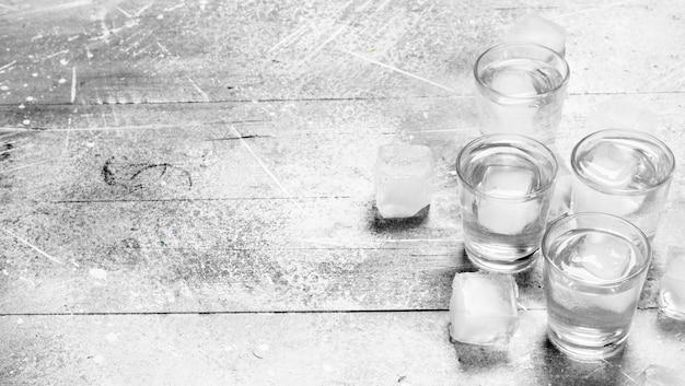 Vodka em um copo e cubos de gelo.