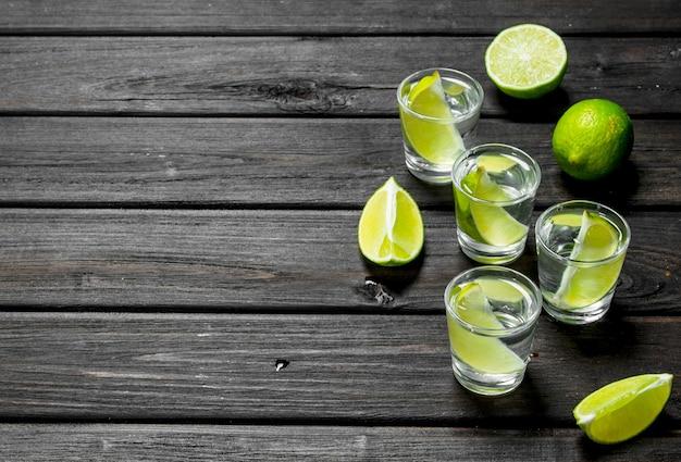 Vodka em um copo e fatias de limão.