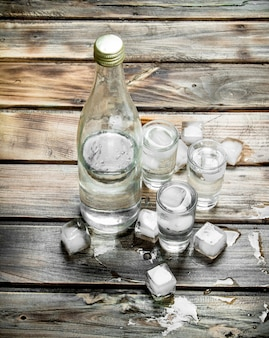 Vodka em uma garrafa e copos de shot com gelo.
