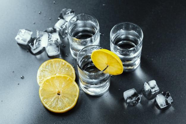Vodka fria em copos de shot em um fundo preto.