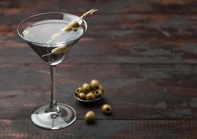 Vodka martini gin coquetel em vidro original com azeitonas em uma tigela de metal e varas de bambu na superfície de madeira. espaço para texto