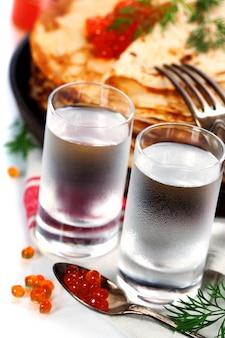 Vodka russa com panquecas e caviar vermelho